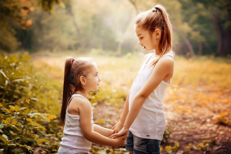 Childhood, family, friendship and people concept - two happy kids sisters hugging outdoors. royalty free stock image