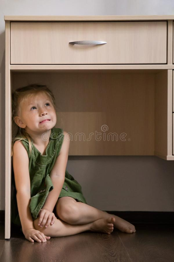 Childhood fears. Scared little girl hiding under the table. Childhood fears. Scared girl hiding under the table stock photo