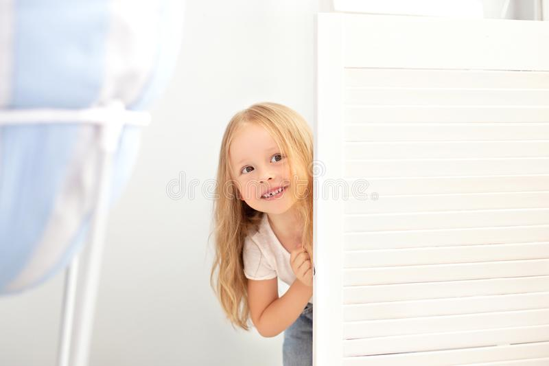 Childhood, fun and people concept - happy smiling beautiful little girl hiding behind room door. The child plays hide and seek at royalty free stock image