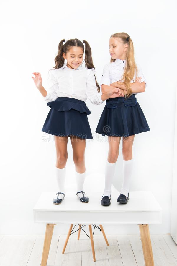 Childhood happiness. School day. Kids cute school students stand on table. On same wave. On the top. Popular girls in stock photo