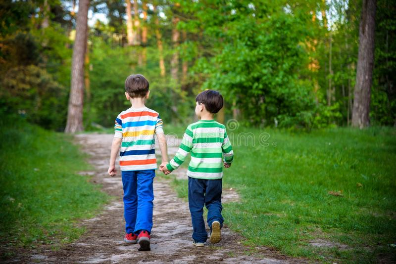 Childhood, hiking, family, friendship and people concept - two happy kids walking along forest path stock image