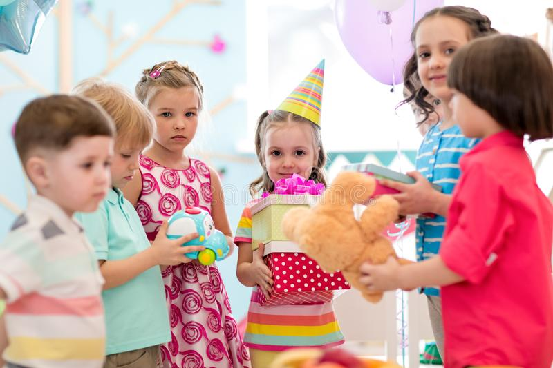 Childhood, holidays, celebration and friendship concept. Happy kids giving gifts at birthday party royalty free stock photo
