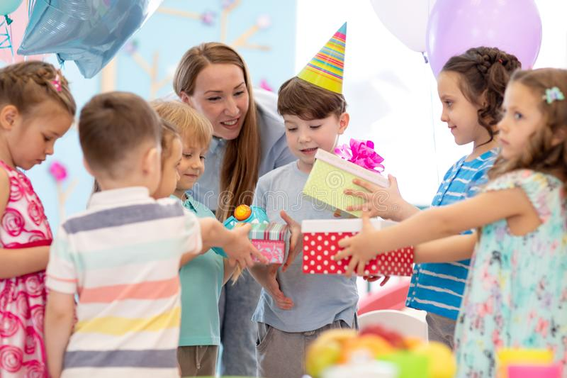 Holidays, childhood and celebration concept - happy friends giving presents to birthday child at party in daycare royalty free stock photo