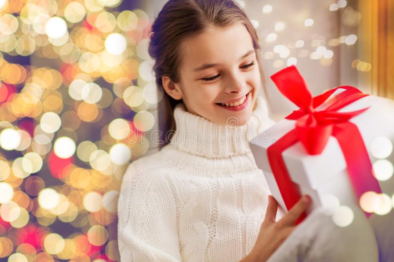 Happy beautiful girl with christmas gift at home royalty free stock images
