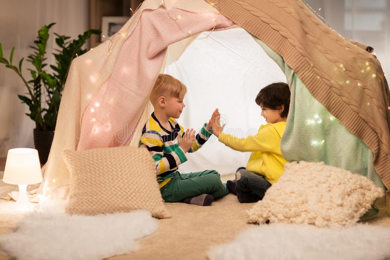 Boys playing clapping game in kids tent at home royalty free stock photography