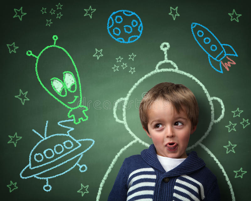 Childhood imagination and dreams. Imagination and dreams of a child, dressed as a space man in front of a blackboard with chalk drawings of space rocket and stock illustration