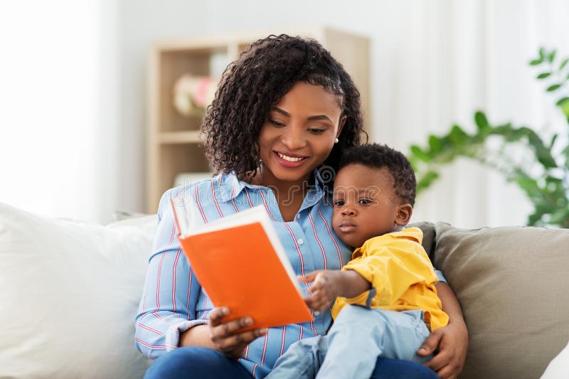 African american mother with book and baby at home royalty free stock photo