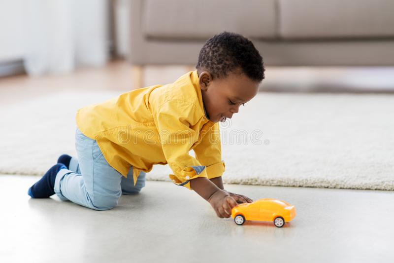 African american baby boy playing with toy car. Childhood, kids and people concept - lovely african american baby boy playing with yellow toy car on floor at royalty free stock images