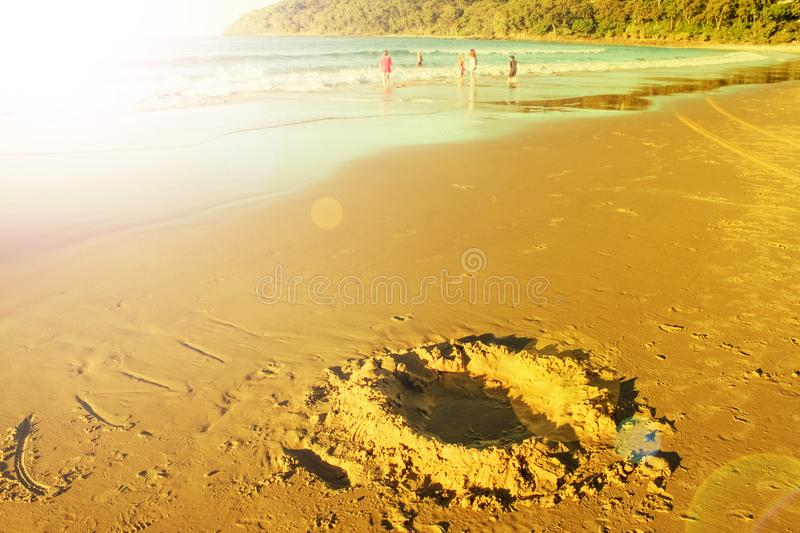 Childhood - Kids playing in the ocean small in background and large hole like moon crater dug in the sand in beach in foreground -. Childhood - Kids play in the stock photos