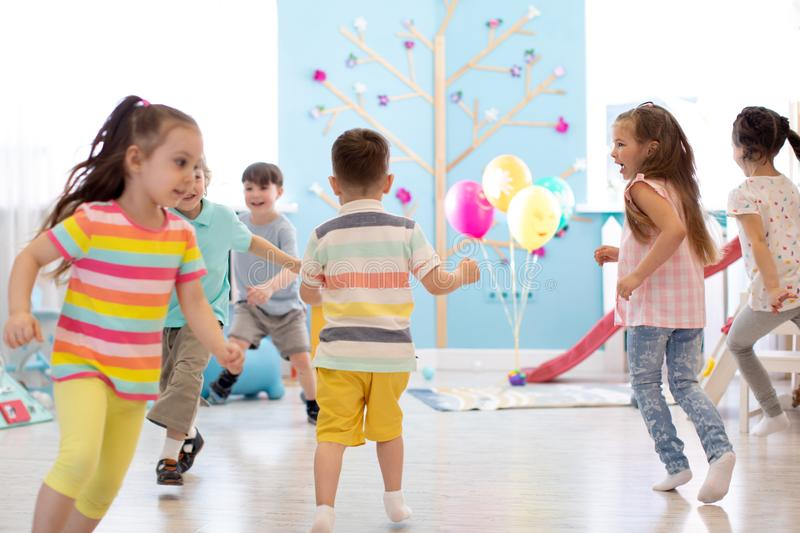 Childhood, leisure and people concept - group of happy kids playing tag game and running in spacious room royalty free stock images