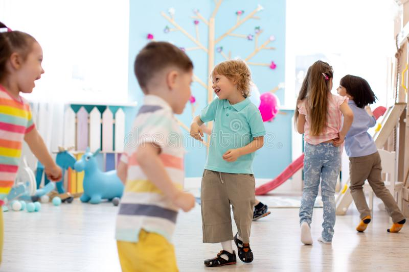 Childhood, leisure and people concept - group of happy kids playing tag game and running in spacious room stock photos