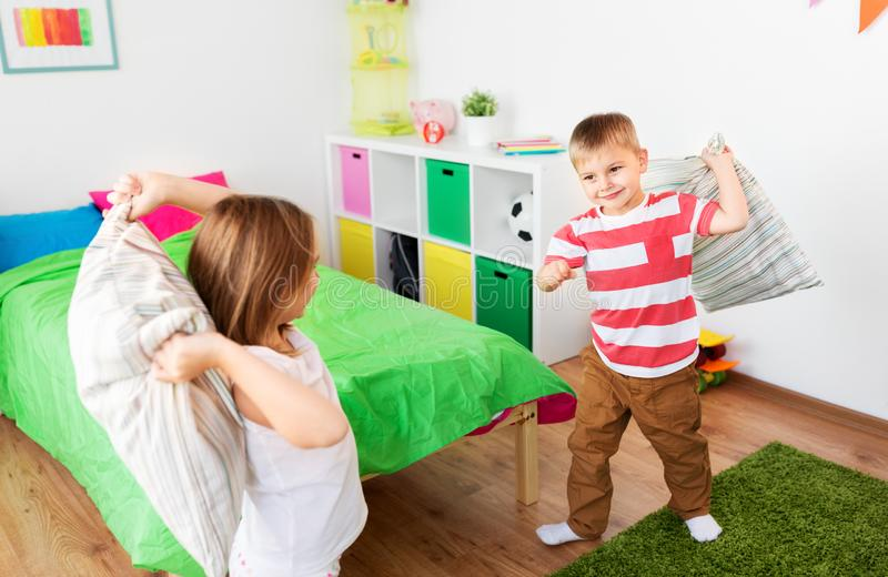 Children playing and fighting by pillows at home royalty free stock photo