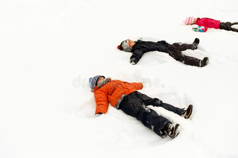 Happy little kids making snow angels in winter royalty free stock images