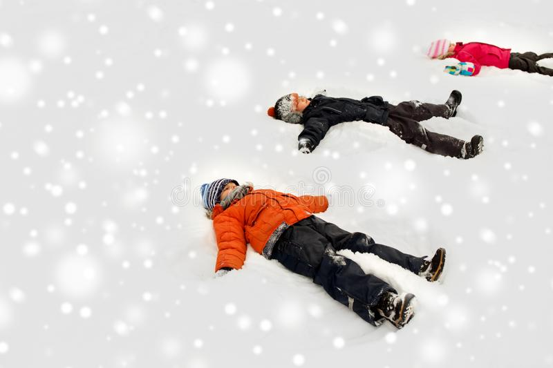 Happy little kids making snow angels in winter royalty free stock photos