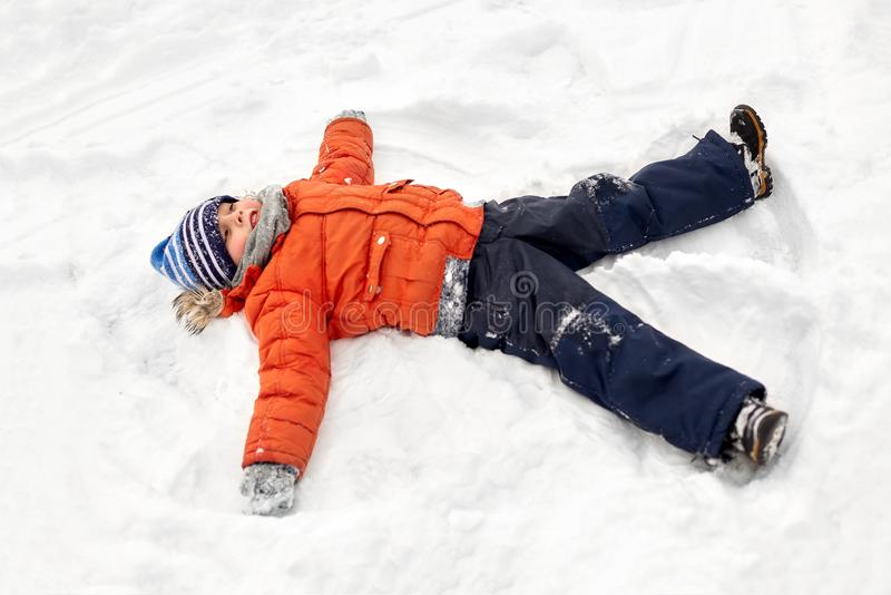 Happy little boy making snow angels in winter stock photo