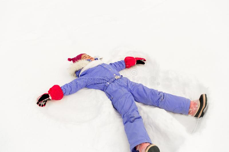 Happy little girl making snow angels in winter royalty free stock image