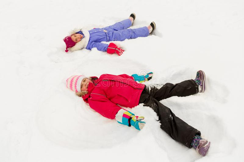 Happy little girls making snow angels in winter royalty free stock images
