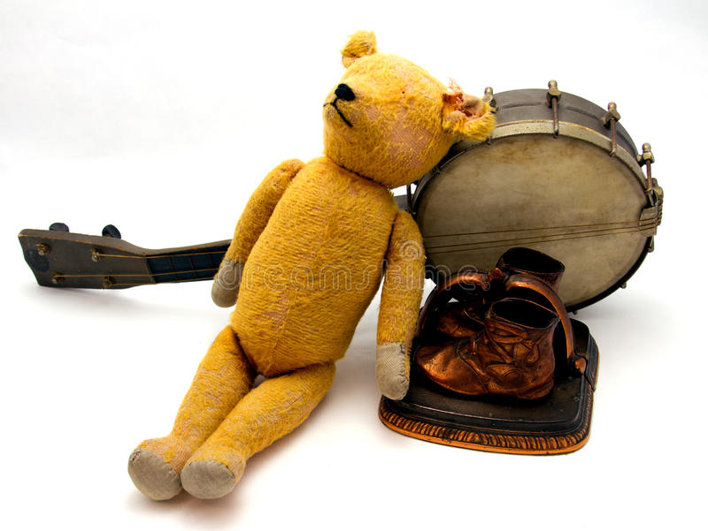 Childhood memories. 1930's childhood memories consisting of an old teddy bear, bronzed baby shoes, and a ukulrele stock image