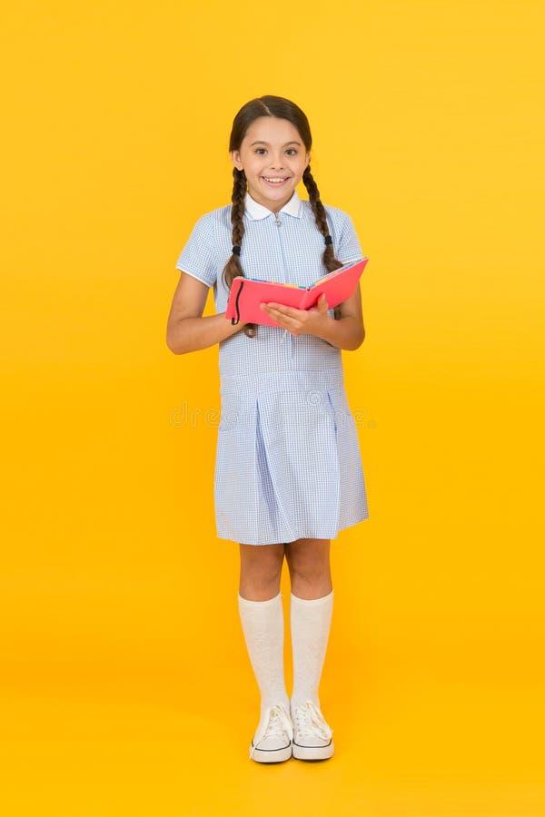 Childhood memories. encyclopedia book for children. girl love literature. old school. happy little girl in retro uniform. Vintage kid fashion. back to school stock image