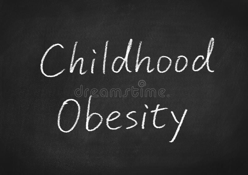 Childhood obesity. Concept words on a blackboard background stock image