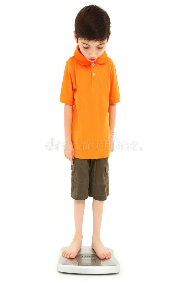 Childhood Onset Anorexia. Adorable eight year old boy on scale very thin anorexia nervosa childhood onset concept royalty free stock photography