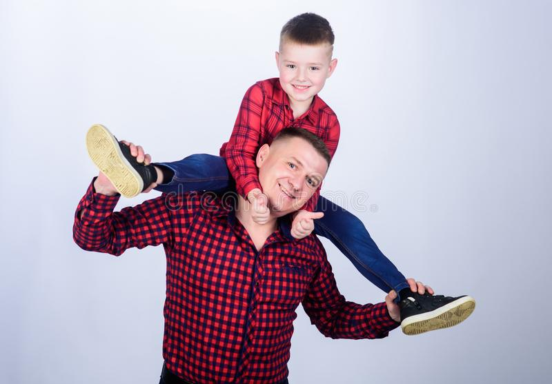 Childhood. parenting. fathers day. happy family. father and son in red checkered shirt. little boy with dad man. Serious. And confident cowboy. Playing together stock photography