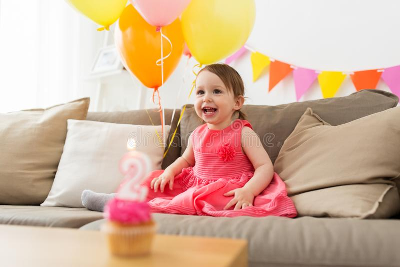 Happy baby girl on birthday party at home. Childhood, people and celebration concept - happy baby girl on birthday party at home stock images