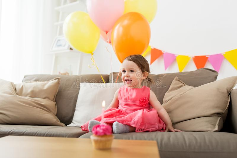 Happy baby girl on birthday party at home. Childhood, people and celebration concept - happy baby girl on birthday party at home stock image