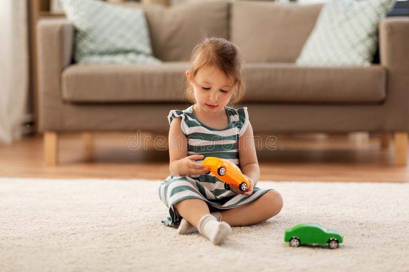 Happy baby girl playing with toy car at home stock images