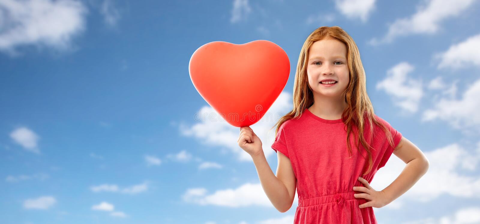 Happy red girl with heart shaped balloon over sky stock images