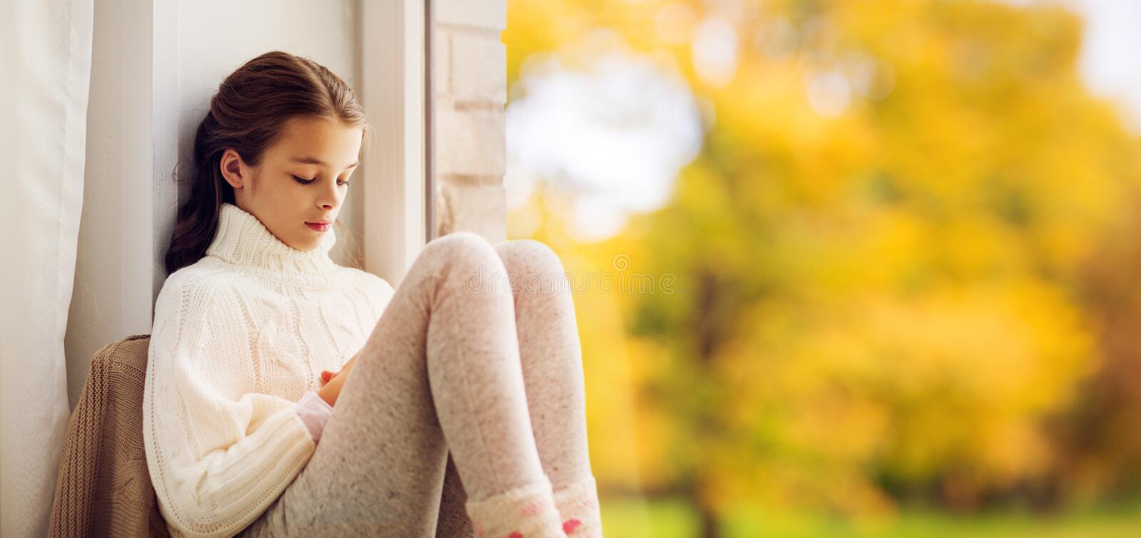Sad girl sitting on sill at home window in autumn stock image
