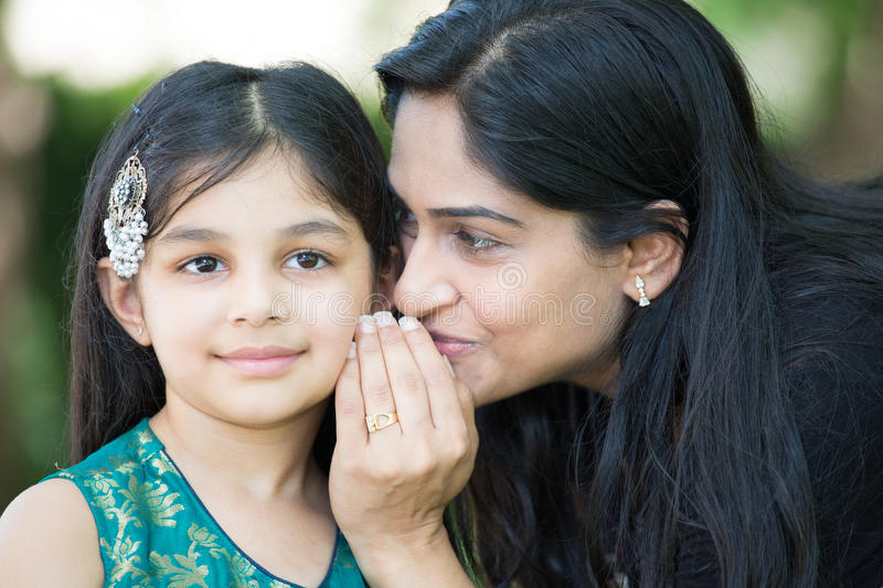 Childhood secrets. Closeup portrait, mom whispering secrets in daughter ear, outdoors outside green trees background royalty free stock photo