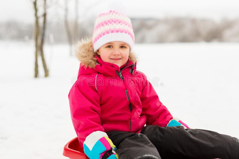 Happy little girl on sled outdoors in winter royalty free stock image