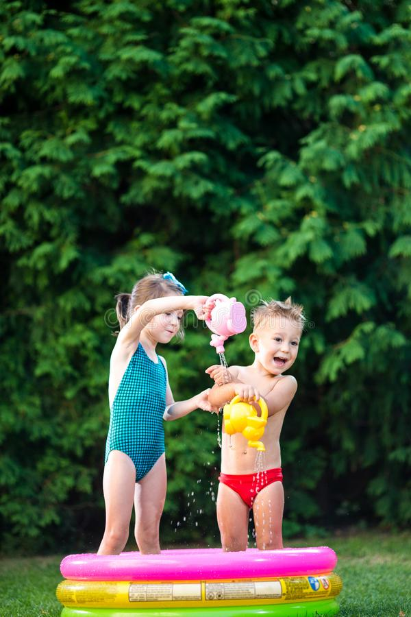 Childhood summer games with water pool. Caucasian brother and sister play with plastic toys watering can pouring water splashing,. Inflatable round childrens stock photography