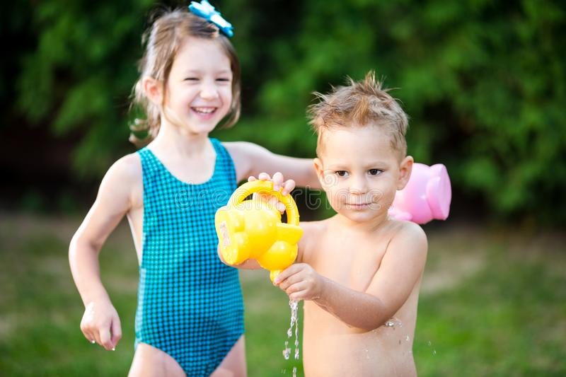 Childhood summer games with water pool. Caucasian brother and sister play with plastic toys watering can pouring water splashing,. Inflatable round childrens royalty free stock image
