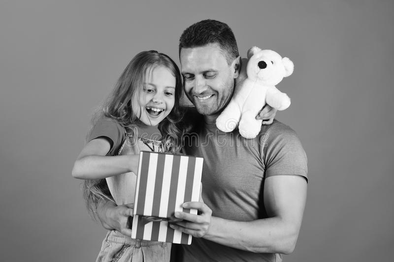 Childhood, surprise gift and family concept. Daughter and father hug. And look into striped box. Schoolgirl and dad hold present box and teddy bear. Girl and royalty free stock image