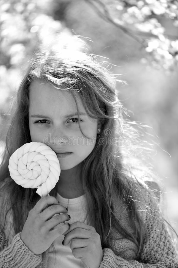 Childhood, sweets and natural beauty concept. Kid in pink sweater holds white lollipop. Schoolgirl with candy walks stock photography