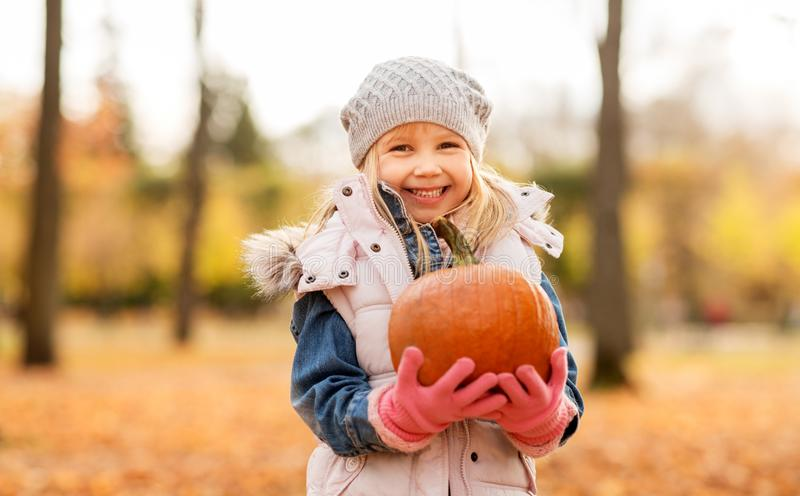 Happy little girl with pumpkin at autumn park royalty free stock photography