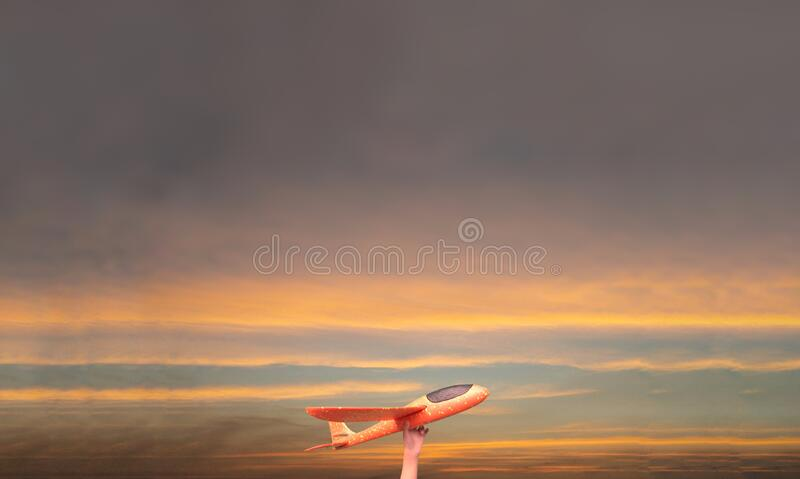 Childhood world travel dreams. Airplane in hand raise up in the background of twilight sky and copy space for text. royalty free stock images