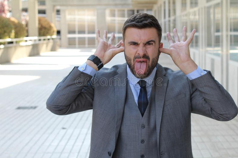 Childish businessman doing an obscene gesture royalty free stock images
