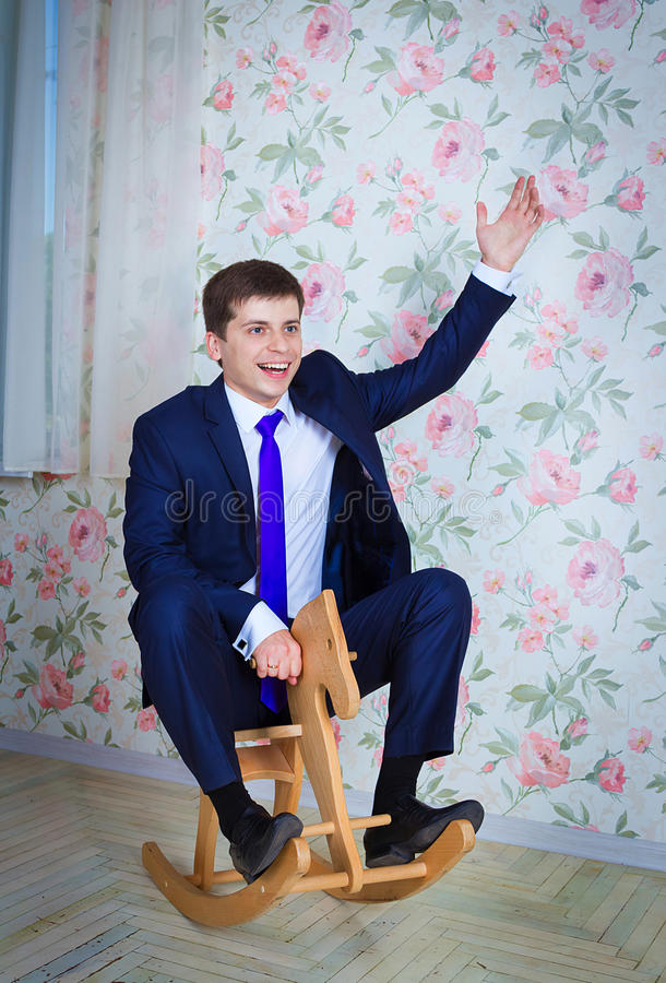 Childish businessman with toy horse. Happy childish young man in business suit riding toy wooden horse. Adult acting like a child concept stock photography
