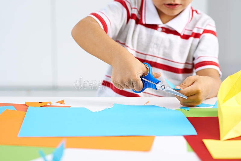 Childish craft. Little boy cutting paper for some craftwork stock photos