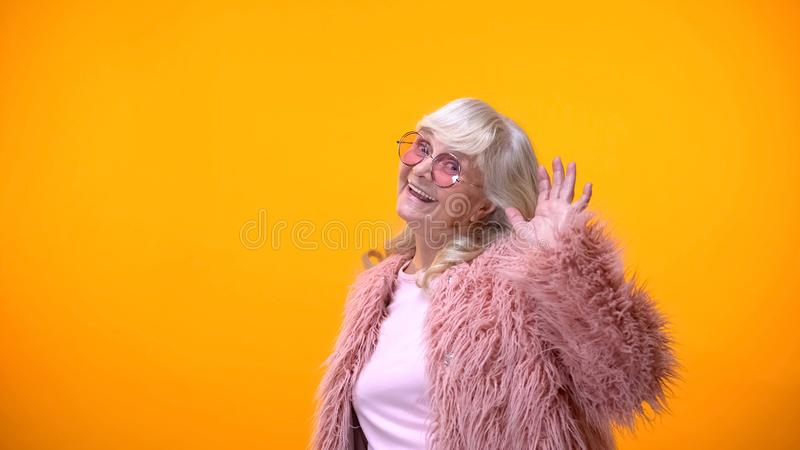 Childish elderly woman in pink coat and round sunglasses smiling into camera stock images