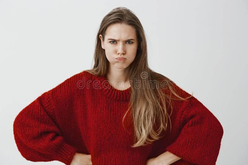Childish girlfriend wants attention. Portrait of displeased offended european woman in red loose sweater, holding hands royalty free stock photos