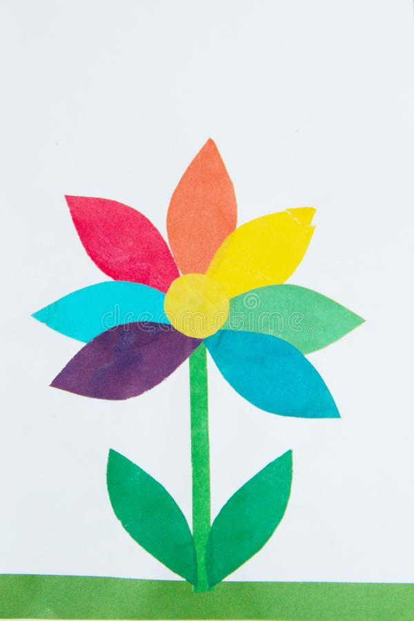 Childish odd job of multicolored flower on green lawn. Child made flower of different colors stock image