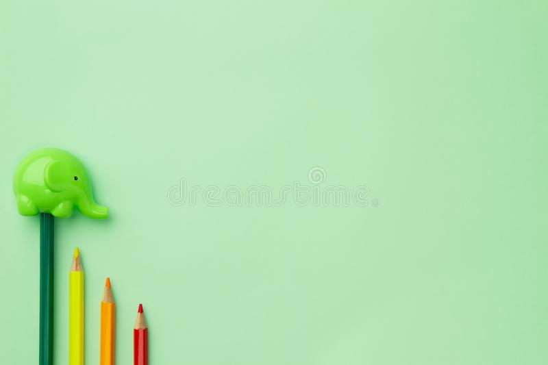 Childish pencil sharpener in the form of an elephant on a pale green background. Childish pencil sharpener in the form of an elephant and four pencils stairs stock photography