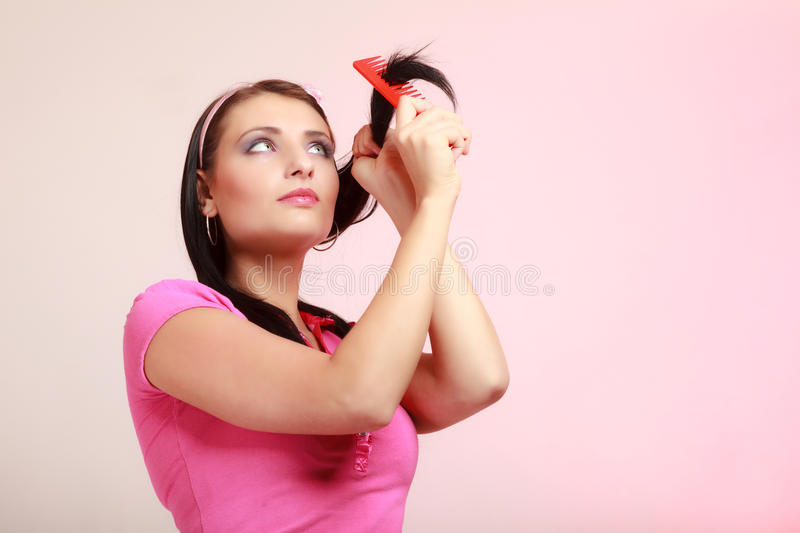 Childish woman infantile girl combing hair. Longing for childhood. Portrait of childish thoughtful young woman combing her hair and dreaming. Infantile pensive stock image