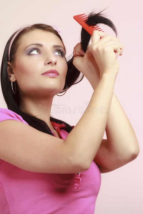Childish woman infantile girl combing hair. Portrait of childish thoughtful young woman combing her hair and dreaming. Infantile pensive girl with comb on pink stock photo
