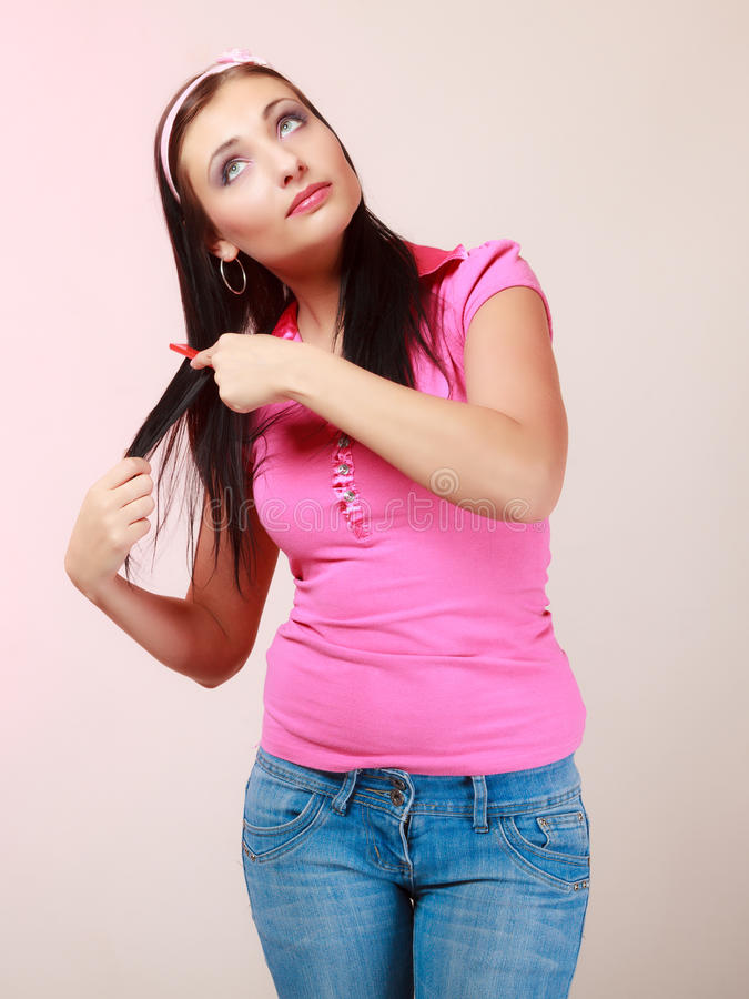 Childish woman infantile girl combing hair. Portrait of childish thoughtful young woman combing her hair and dreaming. Infantile pensive girl with comb on pink stock image