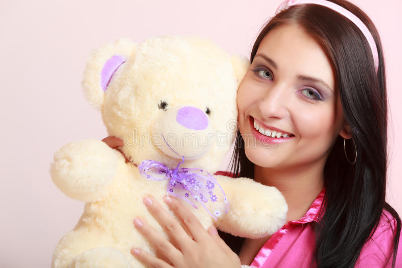 Childish woman infantile girl hugging teddy bear. Portrait of childish young woman with headband holding toy. Infantile girl hugging teddy bear on pink. Longing royalty free stock images